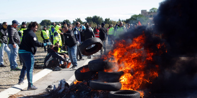 A union member on strike throws a tire on a burning barricade preventing the access to a refinery in Fos sur Mer, southern France, Monday, May 23, 2016. Union-led blockades of French depots and oil refineries have led to fuel shortages and police action. (AP Photo/Claude Paris)